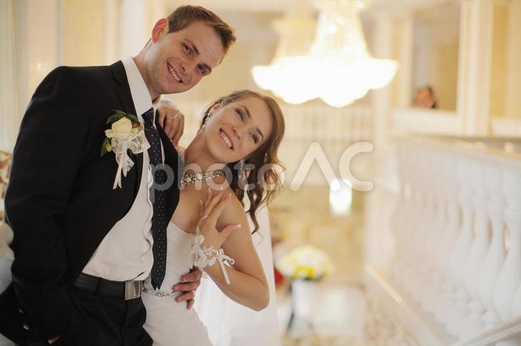 笑顔でカメラを見る新郎新婦の写真
