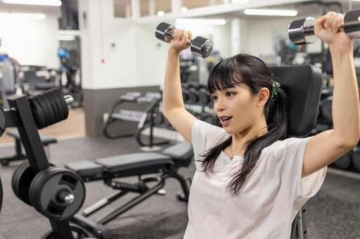 Woman doing muscle training at fitness gym