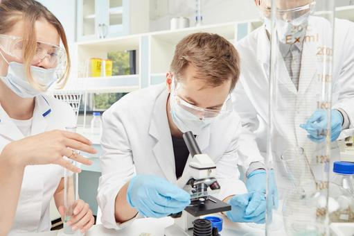Male researcher operating a microscope