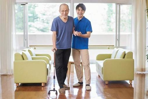 A caregiver who assists the elderly in walking