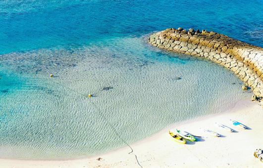 모래 위에 놓인 화려한 카누과 투명한 푸른 바다
