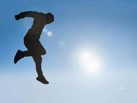 Youth silhouette jumping into the blue sky