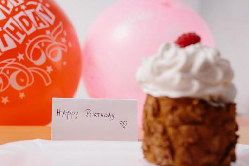 A hand-written birthday card and a birthday balloon with a cake