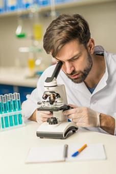 Male researcher peeping at the microscope 11