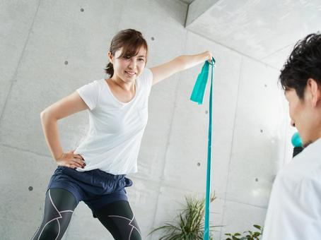 Japanese woman receiving tube training instruction from a personal trainer