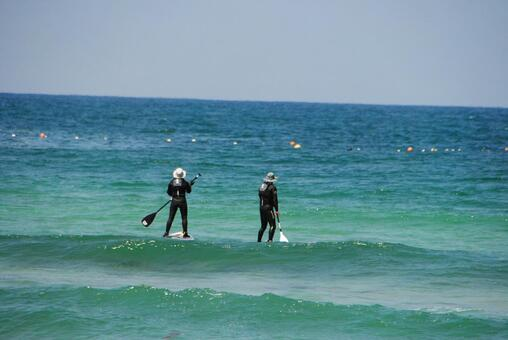Two people playing a stand-up paddle