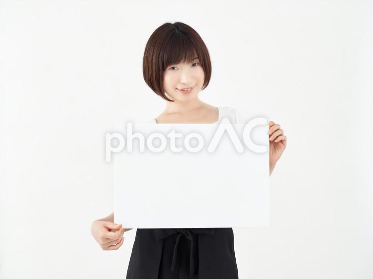 白い背景で白いボードを持つ女性の写真