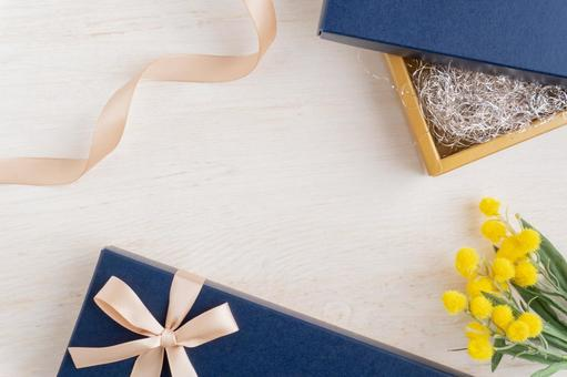 Blue gift box, ribbon and mimosa flowers