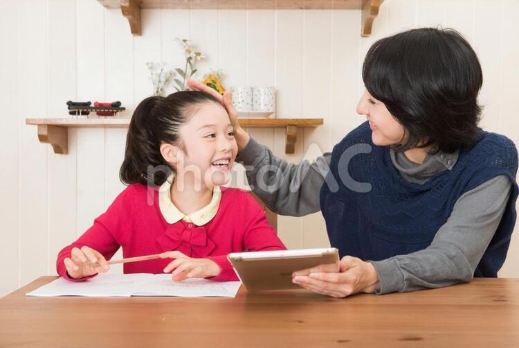 娘の勉強を見るお母さん15の写真