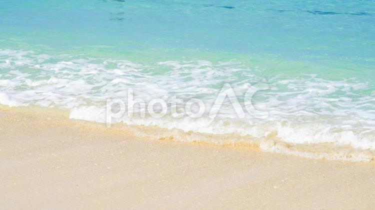 白い砂浜とエメラルドグリーンの海と波の写真