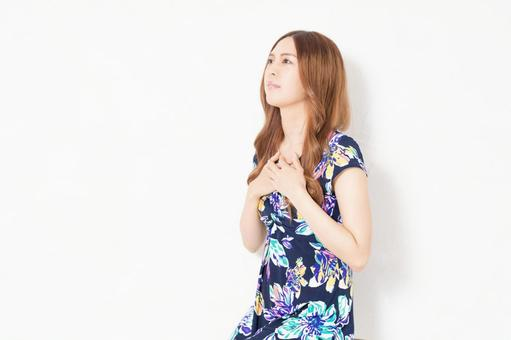 A young woman in a blue dress with her hands on her chest in front of a white wall