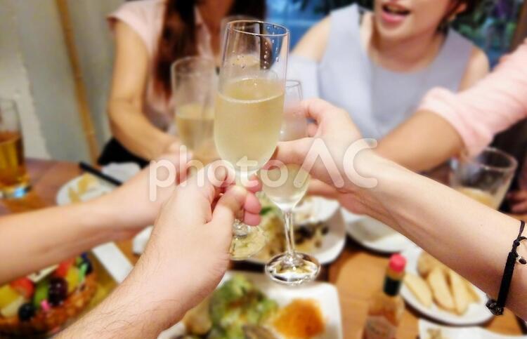 女性と料理が並んだパーティーでシャンパンで乾杯の写真