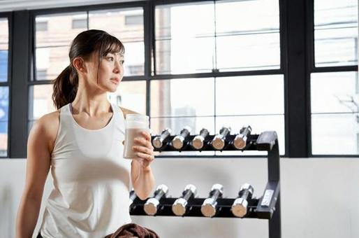 Asian women drinking protein after training