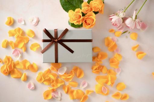 노란색 장미 꽃잎과 선물 상자