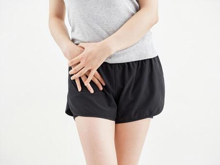 A woman holding a sore hip on a white background