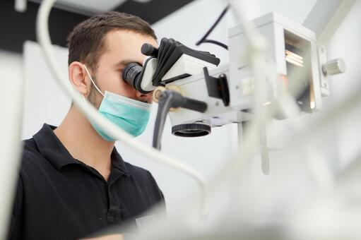 Male dentist with microscope treatment 8