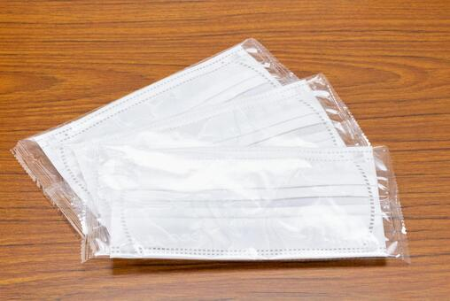Individually wrapped disposable non-woven mask placed on the desk