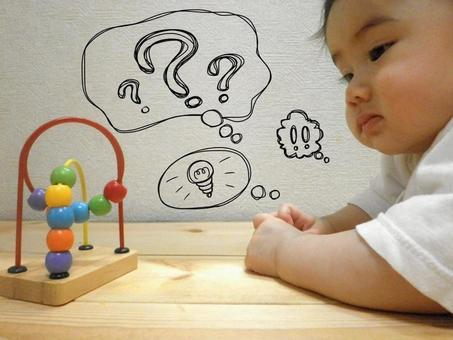 Baby looking at educational toys and thinking