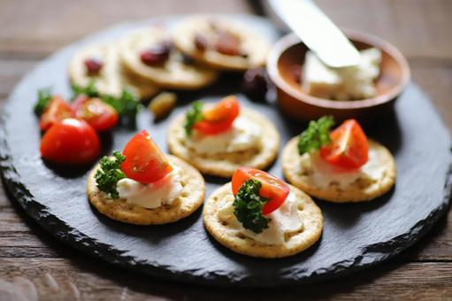 Hors d'oeuvre snacks with crackers, tomatoes, parsley and cream cheese