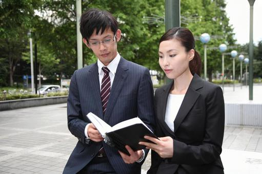 Businessman looking at a notebook, business woman 3