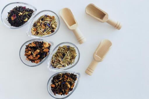 Herbal tea leaves and wooden spoon in a glass container