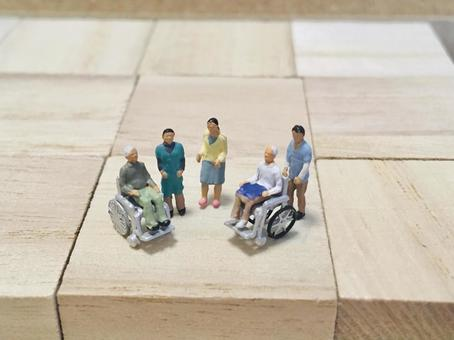 Image of long-term care (elderly people in wheelchairs and caregivers)