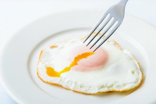 접시에 탄 깨진 계란 후라이와 포크