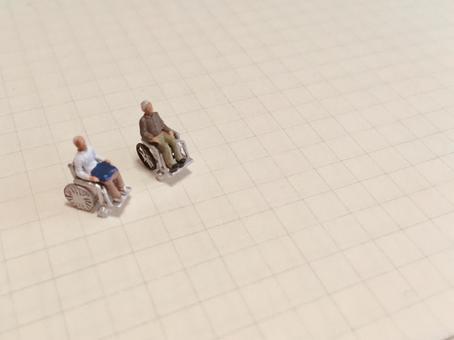 Elderly in two wheelchairs