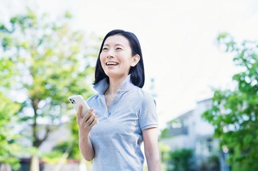Middle woman operating a smartphone outdoors