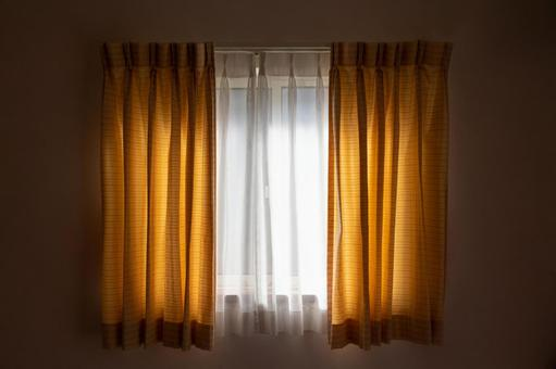 A curtain blocks the sunlight coming in through the window