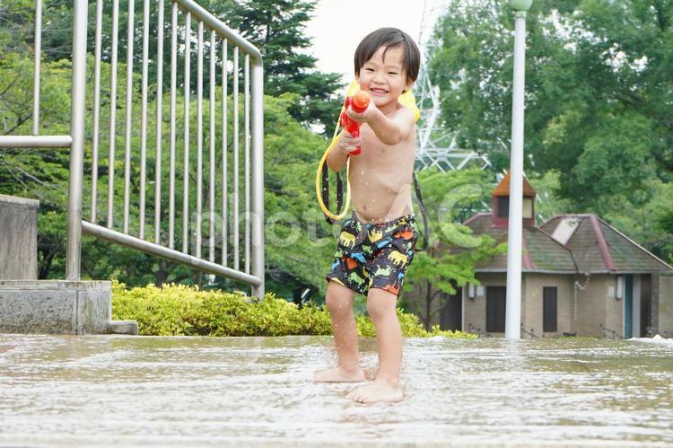 水遊びと水鉄砲で楽しそうな子供の写真
