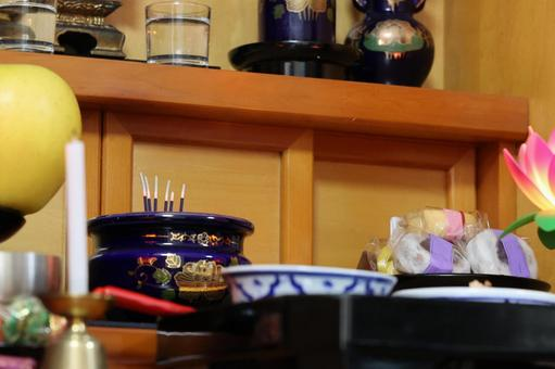 Buddhist altar with Japanese sweets and incense sticks