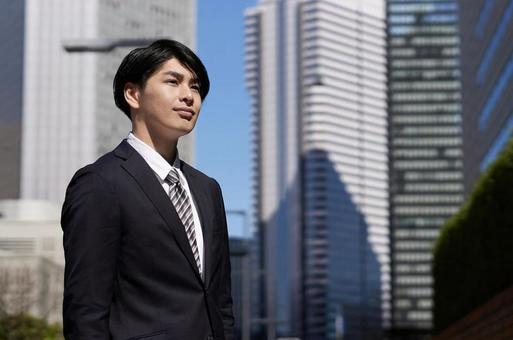 오피스 거리에서 웃는 얼굴로 서 일본인 남성 사업가