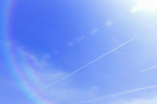 Glittering sunlight and contrails in the blue sky