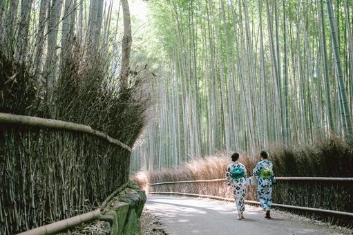 A woman in a yukata walking in a bamboo grove