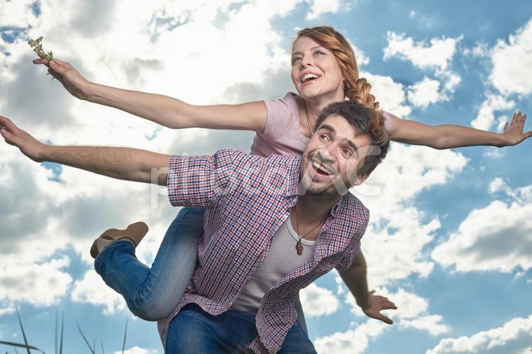 大空に羽ばたくカップルの写真