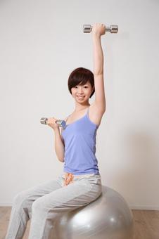 A woman holding a balance ball 20