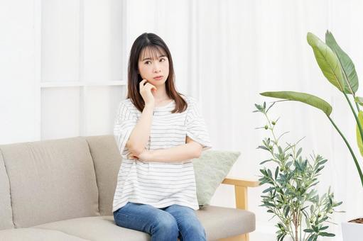 방 소파에 앉아 걱정거리를하는 젊은 여성
