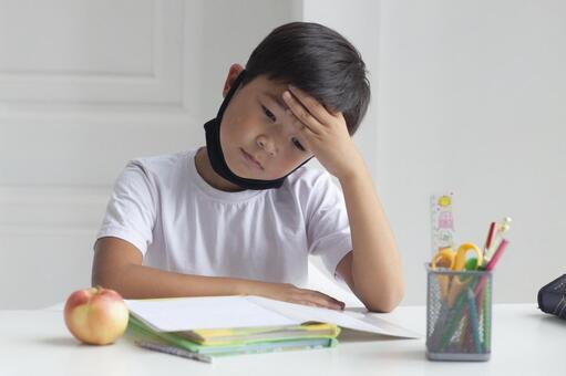男孩戴著口罩和在家學習