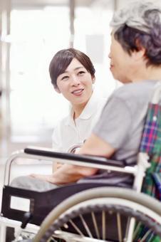 屋内で車椅子に乗っているおばあちゃんと介護士2