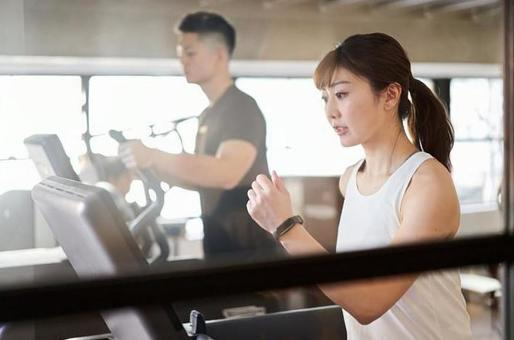 Asian woman running on a treadmill in a training gym