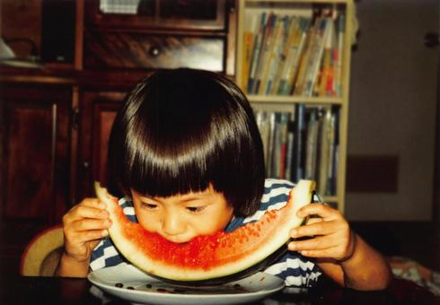 Old film photo girl eating watermelon