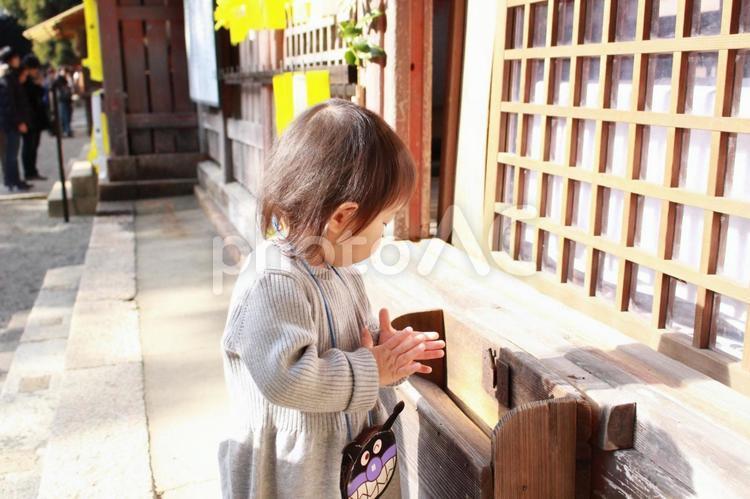 お賽銭を入れて手をあわせる子供の写真
