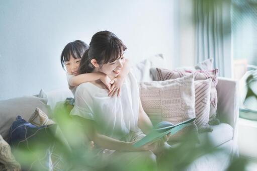 소파에 앉아 그림책을 읽는 부모와 자식