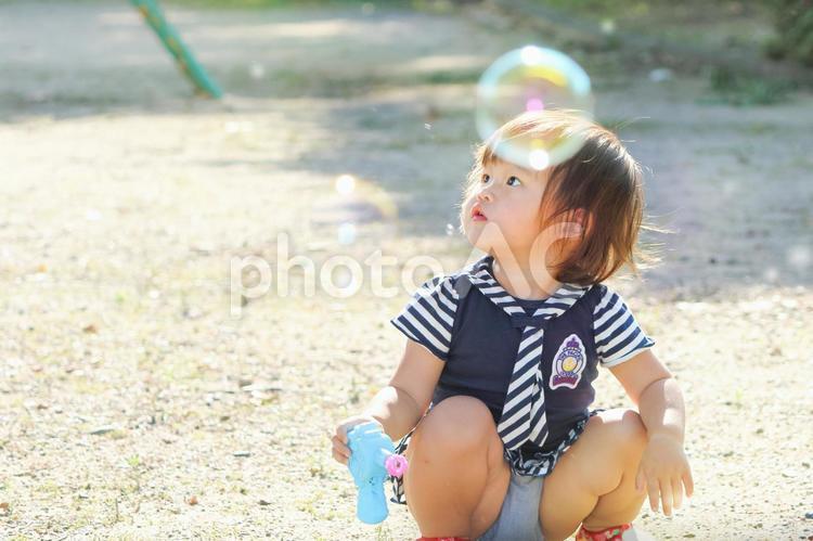 シャボン玉で一人遊びする子供の写真