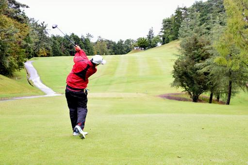 Male golfers wearing rain wear and hitting a tee shot