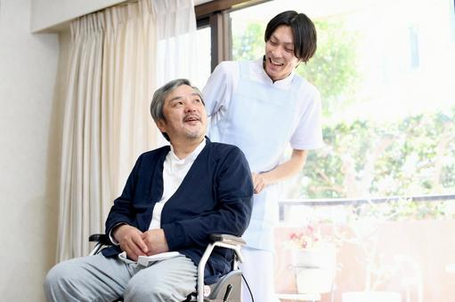 A male caregiver pushing a wheelchair and a smiling senior man