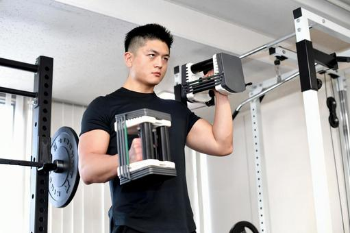 Young man training in the gym (dumbbell curl)