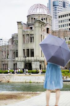 A woman looking up at the Atomic Bomb Dome
