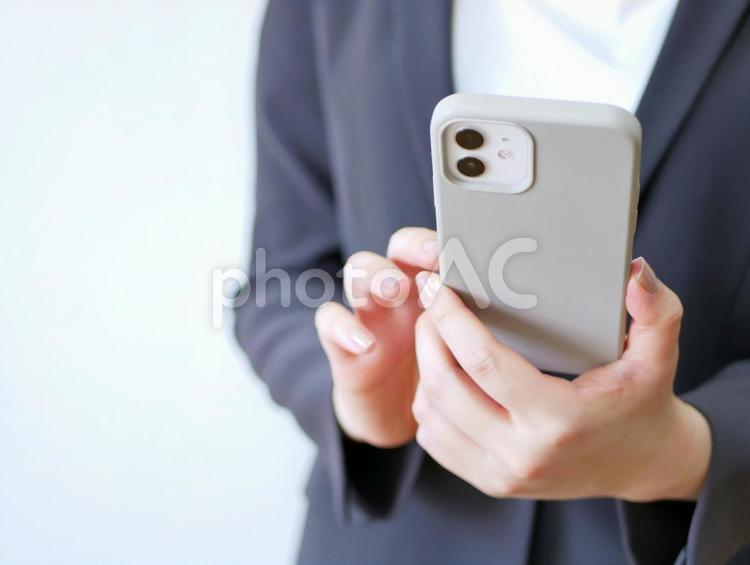 スマートフォンを操作するスーツの女性の写真